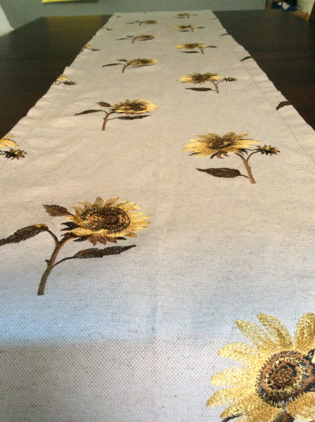 Embroidered sunflower table runner on natural linen like background