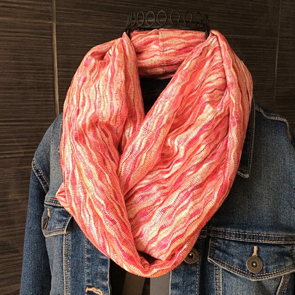 pink and coral subtle wave patterned infinity scarf worn over jean jacket