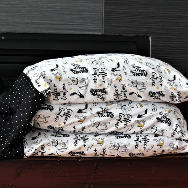 flannel pillowcases on stacked pillows in white with black and gold Paris themed print