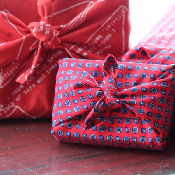 Three gifts wrapped in printed red fabric, tied in Furoshiki style.  The gifts are arranged on a bench on edge with their bows facing forward.