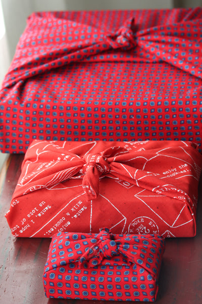 Three gifts wrapped in coordinating patterned red fabric, tied Furoshiki style.  The gifts are lined up on a bench from smallest to largest.