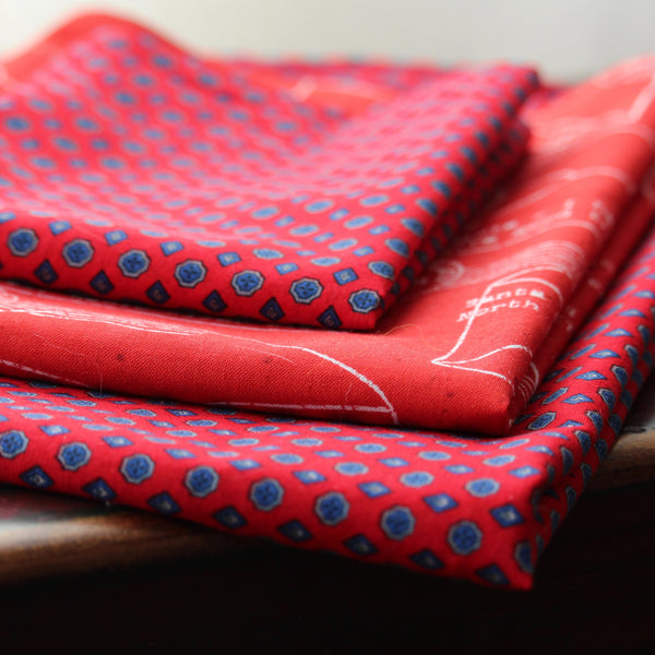Three squares of fabric gift wrap are folded and stacked on a bench.  The squares are coordinated fabrics that are mostly red with blue dots or white writing featuring letters to Santa.