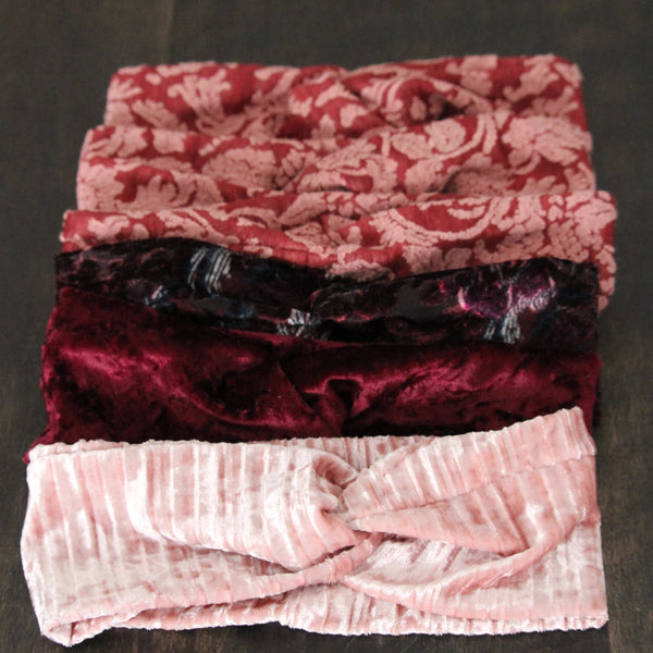 Velvet headbands in pink, rose and cranberry colours, lying on a wooden table