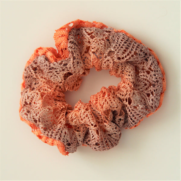 Lace hair scrunchie in gradiated colours from coral to lilac on a white surface