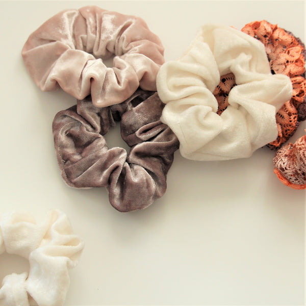 Velvet and lace hair scrunchies scattered on a white surface