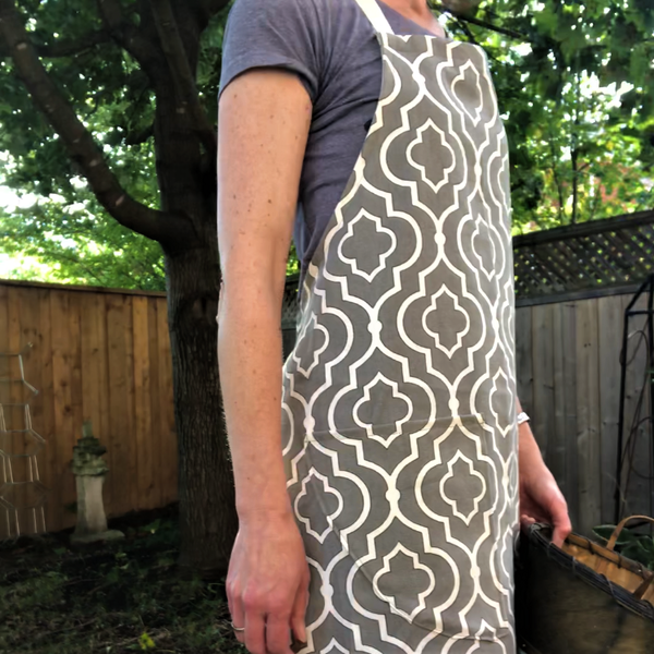 a woman in the garden wearing a full apron in taupe and ivory geometric pattern