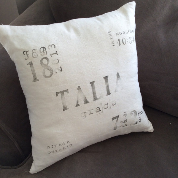 ivory linen ink-stamped birth announcement pillow on chair