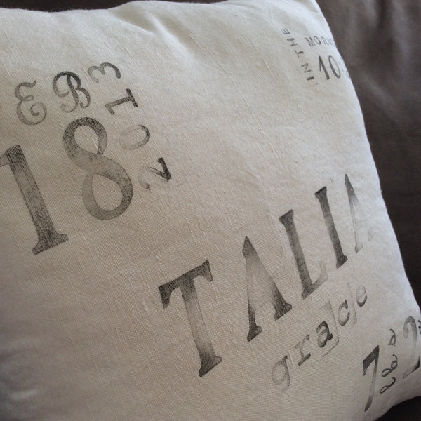 ivory linen ink-stamped birth announcement pillow close up