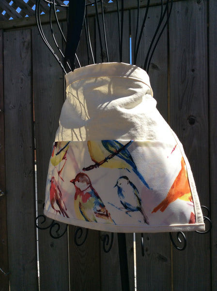 canvas apron with water repellent pockets in colourful bird print, ties at waist
