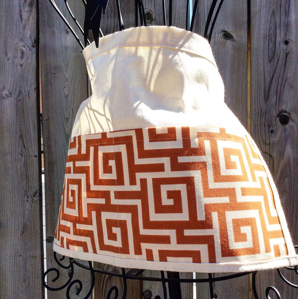 canvas apron with orange meander print has 3 pockets ties at waist