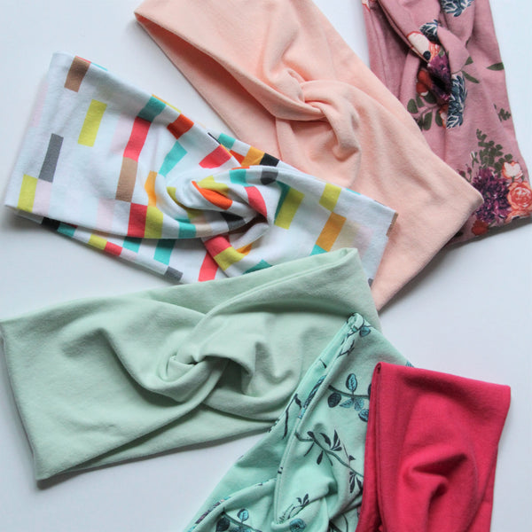 A collection of six jersey knit headbands in spring colours and patterns are fanned out on a white background