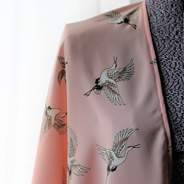 Light pink kimono cardigan with flying cranes close up