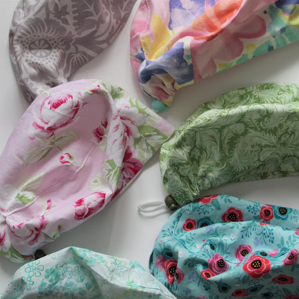 A selection of colourful handmade scrub hats in floral and abstract patterns lie on a white background.