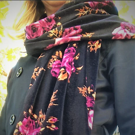 handmade velvet scarf with black and magenta floral pattern worn by a woman beside a tree