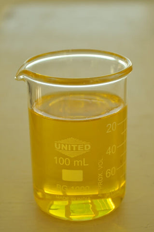 Glass beaker filled with yellow transparent jojoba oil