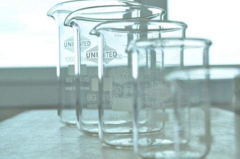 Pretty empty glass measure beakers lined up for making goat milk lotions
