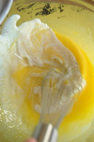 Whisking eggs and sugar in saucepan