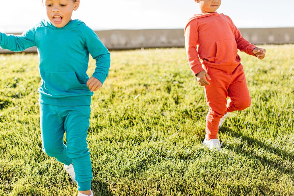 two kids in bamboo fabric playing in grass