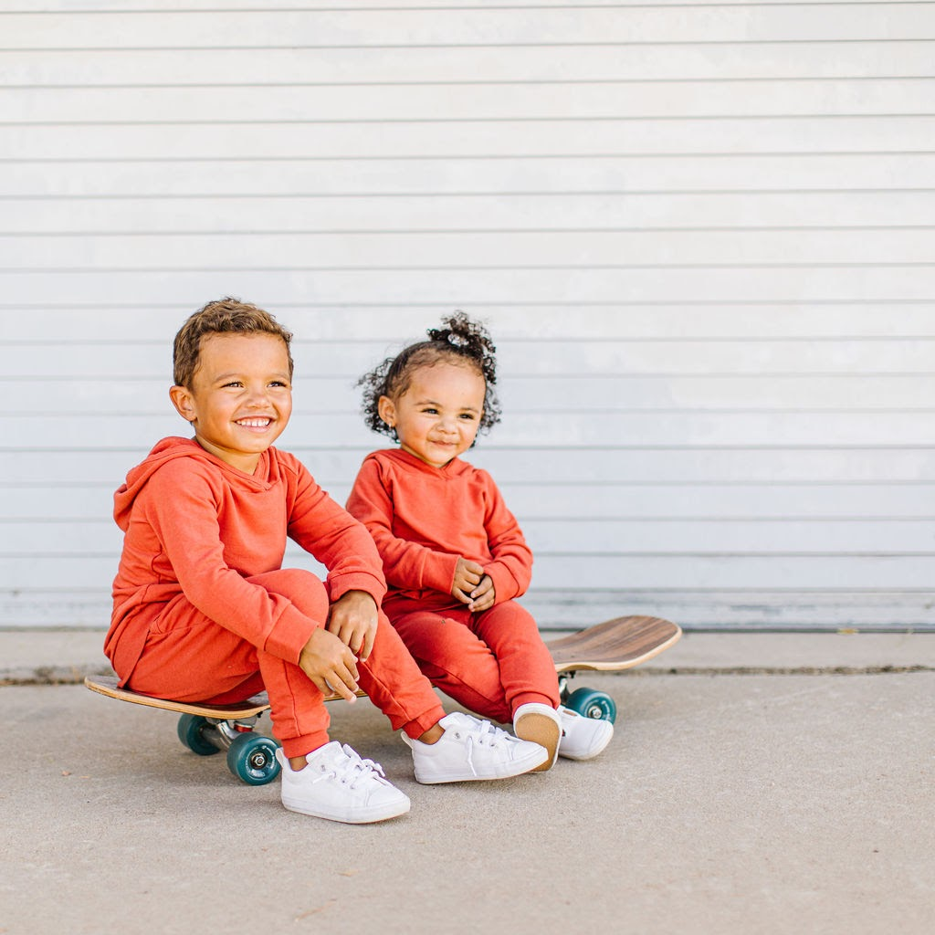 two kids in red sweatsuits sitting on a skateboard