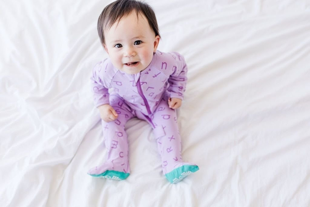 baby in purple footed pajamas