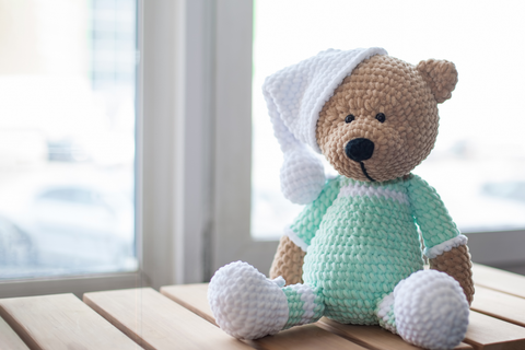 Brown stuffed animal teddy bear in mint-colored clothes and white hat on