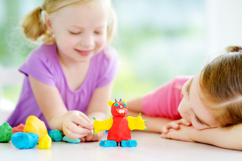Two Cute Little Sisters Having Fun Together with Colorful Modeling Clay