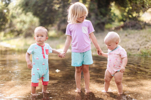a toddler holding the hands of two infants while standing in water