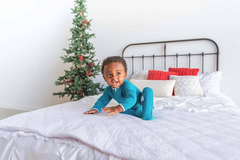 baby in footie pajamas on a bed near a christmas tree