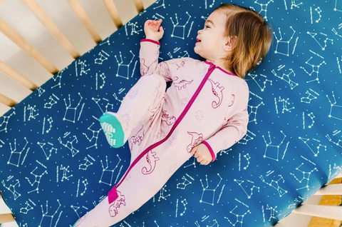 child in pink pajamas lying on blue blanket
