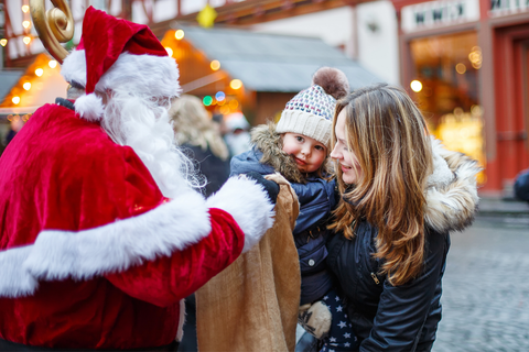 mother holding toddler in front of santa clause
