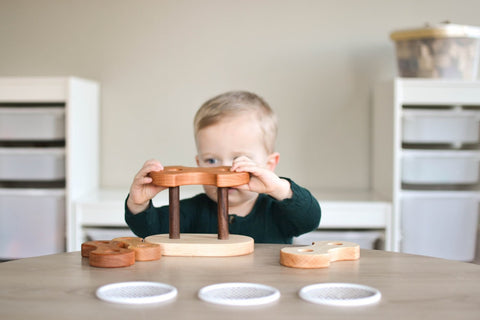 small child playing with wooden stackers