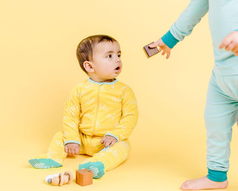 small toddler in blue handing a brown cube to a toddler in yellow