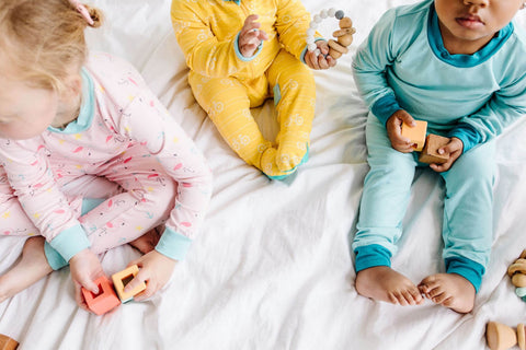 three children playing in bed
