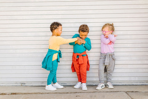 three toddlers dressed in colorful clothes
