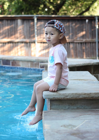 toddler in pink shirt sitting by the pool