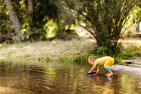 toddler in yellow lark adventurewear clothes playing by a river