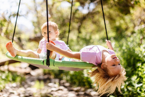 two children dressed in pink playing on a swing