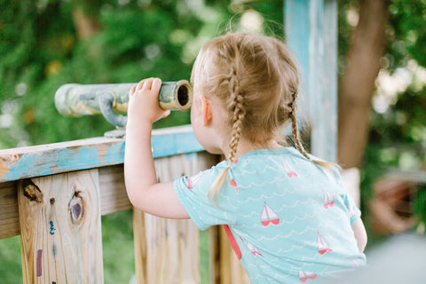 young girl with braided pigtails on a wooden playground
