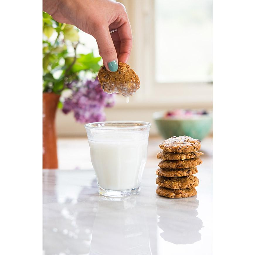 girl dunking granola cookies into milk, country kitchen
