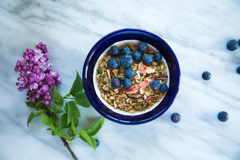 granola in blue bowl on marble slab with blueberries and lilac flower