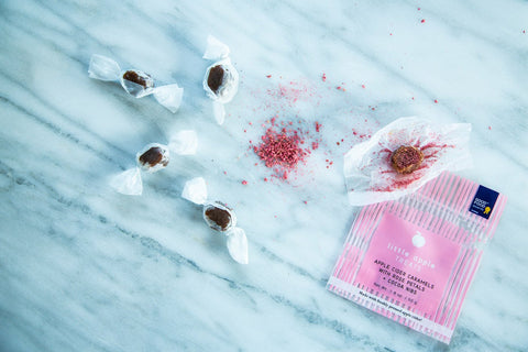 Image of loose caramels with pink apple dust on top rose petals and cocoa nibs