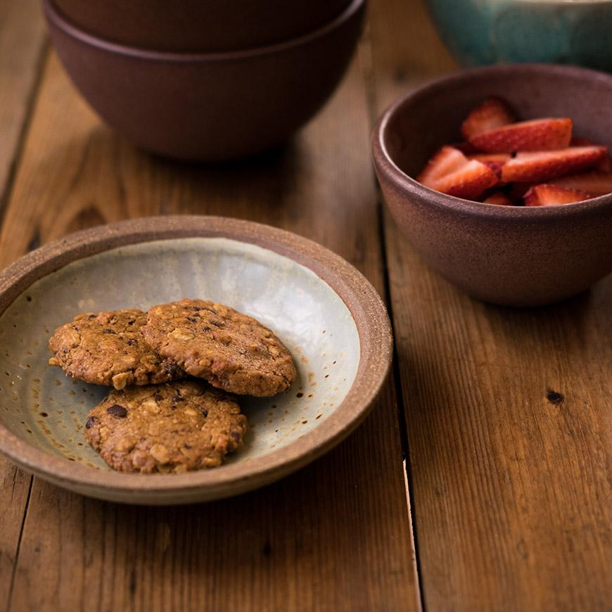 granola cookies in bowl on wood with strawberries