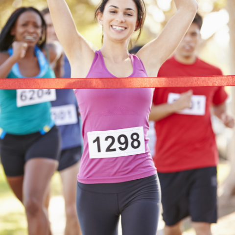 A smiling woman crosses a finish line of a race, there are two other runners behind her