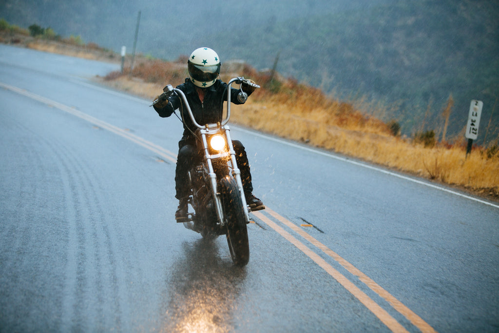 woman on a custom chopper motorcycle riding in the rain in our stratosphere dyneema jumpsuit