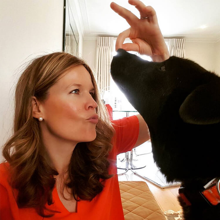 Image of CC holding a Wellness Based Dog Biscuit over a dog's head while she asks for a kiss from him.