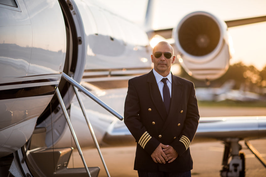 Private Jet Pilot standing with jet