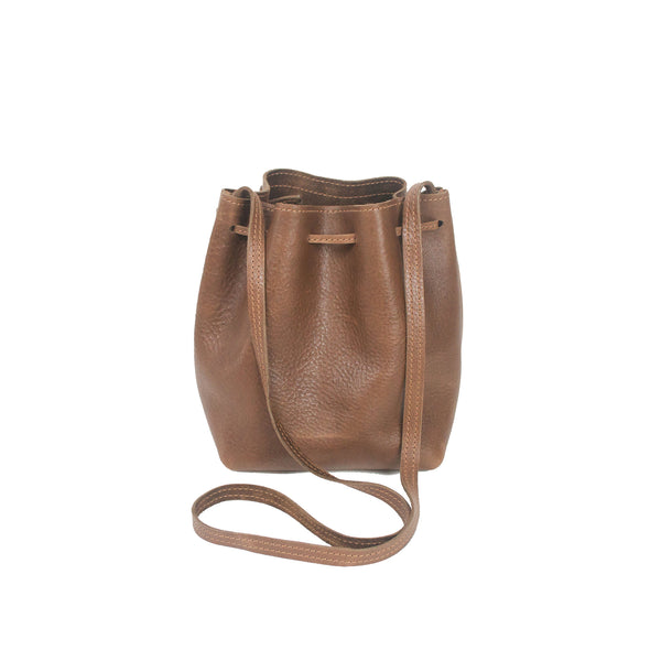 Handmade leather bucket bag with slide closure and two front tassels.  Perfect size for you essentials with enough room to stuff in a small layer.