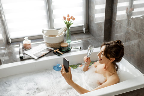 women taking a bath having an at home spa while drinking wine