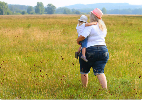 Mother carrying her son in a field
