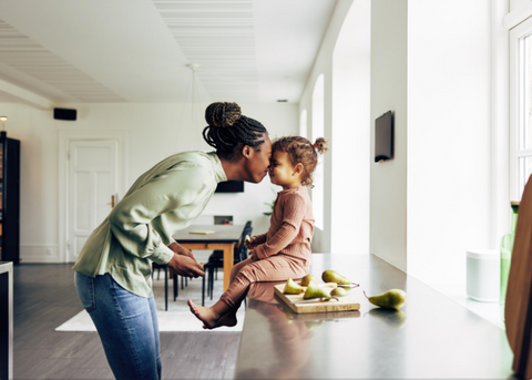 Mother kissing her child in the kitchen.